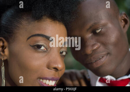 Close-up of faces of young couple in love with heads stuck against each other. - Stock Image
