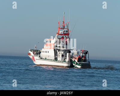 Tender o a maritime emergency rescue cruiser gets pulled up to main ship, skill presentation at wharf of Zingst - Stock Image