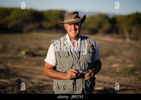 Happy man standing with camera during safari vacation - Stock Image