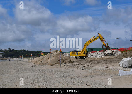 Longrock, Cornwall, UK. 14th June 2019. UK Weather. Diggers out on a sunny afternoon on the beach at Longrock near Marazion, as an EU funded program to improve sea defences in the area continues.  Credit Simon Maycock / Alamy Live News. - Stock Image