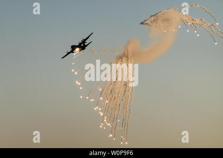 Hazerim Air Base, Israel. 27th June, 2019. A Lockheed Martin C-130J Super Hercules turboprop transport aircraft releases flares to divert incoming heat seeking missiles at an air show at a graduation ceremony honoring newly certified Israel Air Force pilots and navigators following their successful completion of one of the most competitive and rigorous training processes in the IDF at Hazerim Air Base in the Negev Desert. Credit: Nir Alon/Alamy Live News. - Stock Image