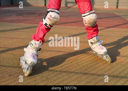 Kyiv UA, 21-04-2019. Close-up of feet child shod in roller blades, active girl riding roller skates on special sports area near the house - Stock Image