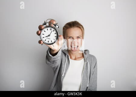 Portrait Handsome Young Woman Posing Blank White Background.Pretty Girl Screaming Holding Vintage Alarm Clock Hand - Stock Image