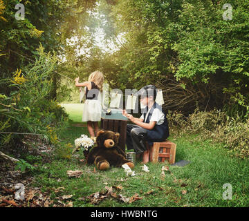Creative school children are working and writing a story book on a typewriter with paper outside for an education, - Stock Image