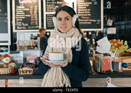 Winter portrait of young beautiful woman in knitted scarf, fur ears, warm sweater with cup of coffee. Girl standing near bar counter in coffee shop. - Stock Image