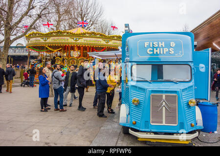 Men women holiday makers and tourists queuing for fish and chips from a Citroen van on the South bank of the river Thames London England - Stock Image