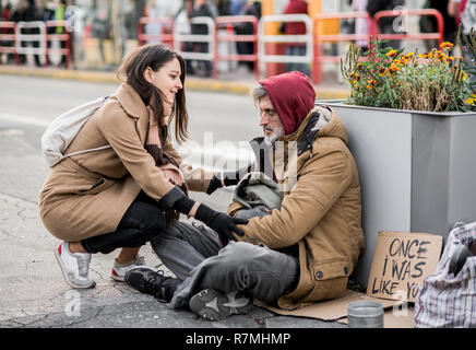 A young woman giving money to homeless beggar man sitting outdoors in city. - Stock Image