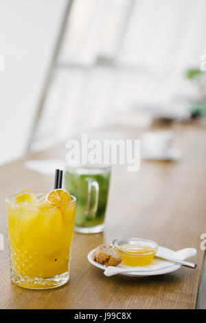Orange juice close up with jam and some dounts and green tea in the backgroundù - Stock Image