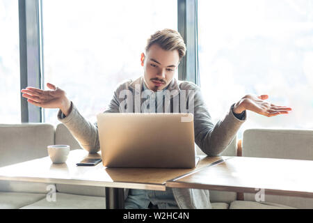 I don't know!Portrait of confused handsome bearded young freelancer in grey blazer are sitting in cafe and making video call on laptop with raised arm - Stock Image