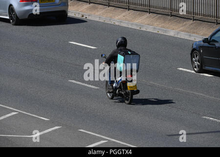 A deliveroo rider delivering a food package on a moped driving along a dual carriageway with copy space taken from above. - Stock Image