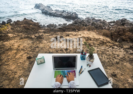 Alternative unusual happy destop technology business workstation with ocean view - digital nomad concept lifestyle for modern people - laptop and tabl - Stock Image