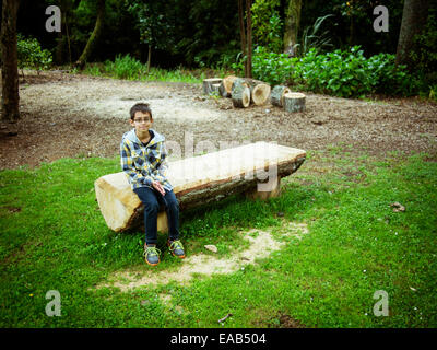 Boy sits on sawn log bench in park - Stock Image