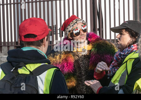 London, UK. 19th December 2018. An American in a Christmas costume with santa hat and Christmas pudding sunglasses goes to talk with the small group of extreme right Brexiteers wearing high-viz vests protesting outside parliament calling for an immediate Brexit. Afterwards I heard him tell the two filming him that he had been very frightened. Credit: Peter Marshall/Alamy Live News - Stock Image