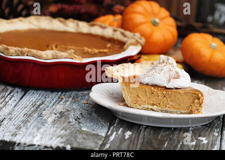 Slice of homemade pumpkin pie over a rustic wooden background. Extreme shallow depth of field with selective focus. - Stock Image