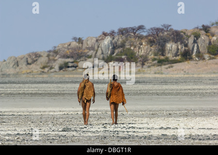 San bushman trackers walking across the cracked pan towards the ancient granite outcrop of Kubu Island (Lekhubu), - Stock Image