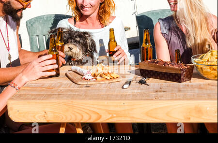 Close up with group of cheerful happy friends people men and women eating and drinking together on a wood table -  nice dog looking the food with hope - Stock Image