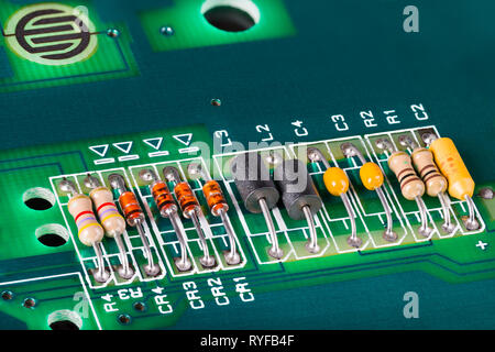Inductors, capacitors, resistors and diodes on PCB. Colorful electronic components detail. Green circuit board. Button switch. Open computer keyboard. - Stock Image