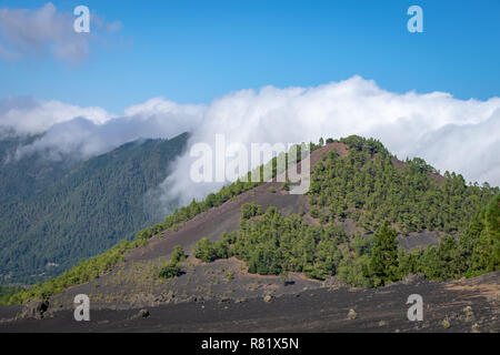 Clouds rolling over the volcanic blast crater ridge at Llanos del Jable, La Palma, Canary Islands, Spain - Stock Image
