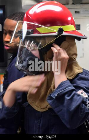 180825-N-QR145-054  MEDITERRANEAN SEA (Aug. 25, 2018) - Boatswain's Mate 3rd Class Tanya Riker, right, dons a firefighting helmet during engineering and damage control drills aboard the Arleigh Burke class guided-missile destroyer USS Ross (DDG 71) in the Mediterranean Sea, Aug. 25, 2018. Ross, forward-deployed to Rota, Spain, is on its seventh patrol in the U.S. 6th Fleet area of operations in support of U.S. national security interests Europe and Africa. (U.S. Navy photo by Mass Communication Specialist 3rd Class Krystina Coffey/ Released) - Stock Image