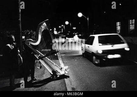Large concert harp being pushed across road at small eisteddfod in village hall Talsarnau Gwynedd Wales UK - Stock Image