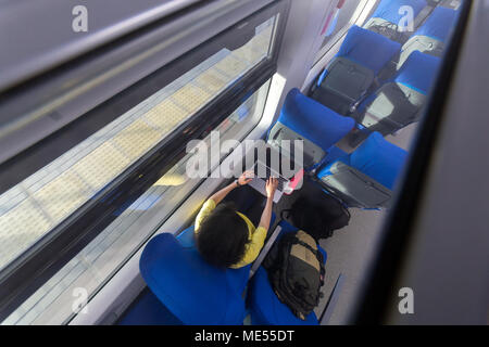 young woman loking in laptop during traveling in train view from above - Stock Image