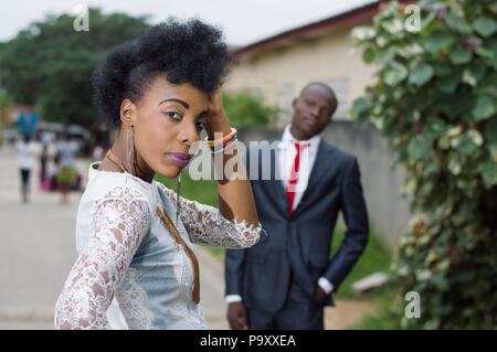 Young woman looking back and admired by her man in the street - Stock Image