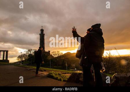 A couple take a selfie as the sun rises over Carlton Hill in Edinburgh - Stock Image