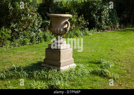 Garden ornament, stoneware urn on plinth. Lawn, spring bulbs in background. At Milntown, period house and garden. - Stock Image