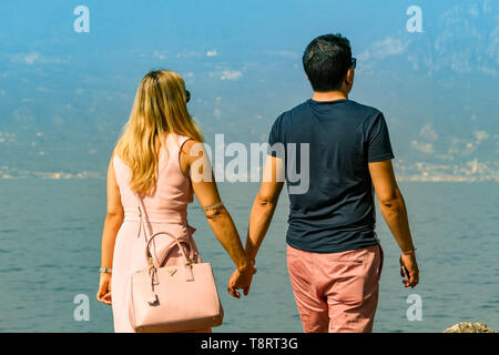TORRI DEL BENACO, LAKE GARDA, ITALY - SEPTEMBER 2018: Two people walking hand in hand on the edge of Lake Garda in Torri del Benaco - Stock Image