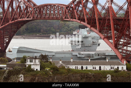 The aircraft carrier HMS Queen Elizabeth passes under the Forth Rail Bridge as it leaves the Firth of Forth following maintenance at the Rosyth Dockyards. - Stock Image