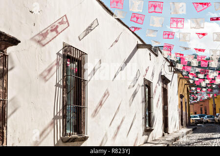 Paper fiesta banners cast a shadow across a wall along Calle Aparicio in the historic district of San Miguel de Allende, Mexico. - Stock Image