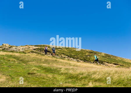 Three walkers approach each other on the footpath leading south from the summit of  Cat Bells (451 metres) near Keswick, Cumbria. - Stock Image