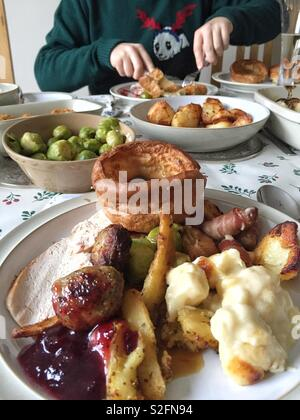 A Christmas dinner table with plates full of festive food including sprouts turkey and Yorkshire pudding. - Stock Image