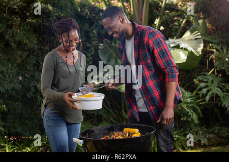 A couple barbecuing together - Stock Image