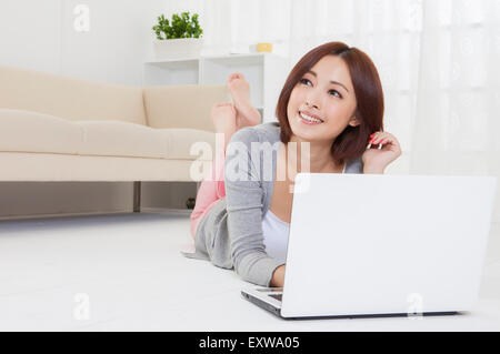 Young woman lying down on front and using laptop, - Stock Image