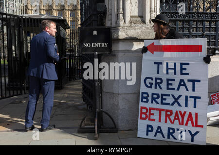 On the day that MPs in Parliament vote on a possible delay on Article 50 on EU Brexit negotiations by Prime Minister Theresa May, George Eustice, MP for Camborne, Redruth & Hayle, exchanges words with Brexiteer activists as they protest at the gates of the House of Commons, on 14th March 2019, in Westminster, London, England. - Stock Image
