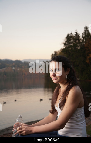 A  young woman in fitness attire holding a plastic disposable water bottle alongside lake. - Stock Image