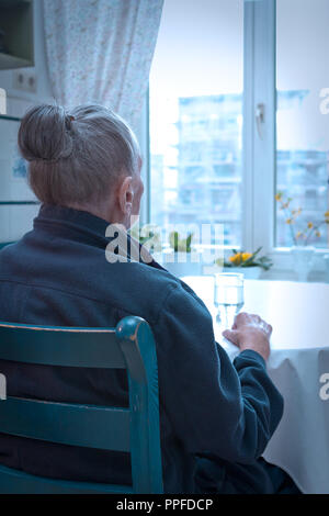 Old woman sitting alone at her kitchen table looking out of the window, blue filter effect, concept of old-age depression, loneliness - Stock Image