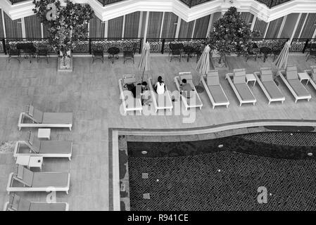 Hotel swimming pool with people sat around the  engrossed with their smartphones.  Black and white photography - Stock Image