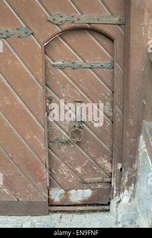 old door with hand made iron hinges and knocker - Stock Image