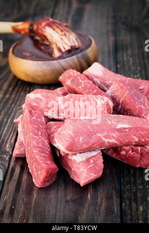 Uncooked raw boneless beef ribs with bowl of barbecue sauce and bbq sauce mop over top a rustic wood table / background. Image shot from overhead view - Stock Image