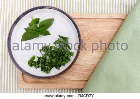 Whole and chopped fresh basil leaves on a plate - Stock Image
