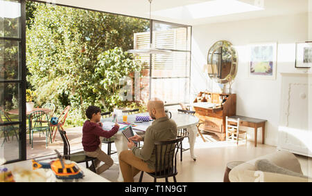 Father and son using digital tablet and coloring at dining table - Stock Image