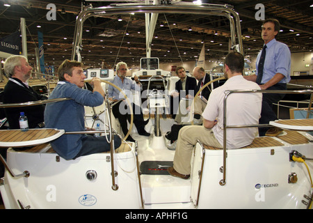 Group of men holding a meeting on the deck of a yacth at the lnodon boat show - Stock Image