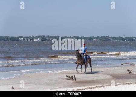 Girl horseback riding on the shoreline of Jekyll Island, Georgia USA - Stock Image