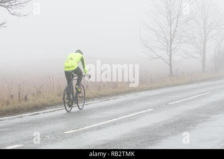 Strathblane, Stirlingshire, Scotland, UK - 6 January 2018: UK weather - a cyclist on a foggy but mild morning in Strathblane, Stirlingshire Credit: Kay Roxby/Alamy Live News - Stock Image