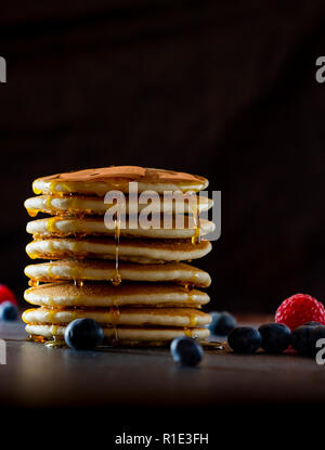 tall stack of pancakes with syrup and blueberry and raspberry fruit - Stock Image