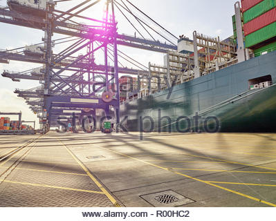 Empty dockyard with container ship and cranes waiting to load merchandise - Stock Image