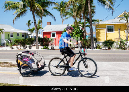 Sanibel Island Florida Castaways Beach & Bay Cottages resort hotel man boy child father son children cycling bicycle trailer pedaling - Stock Image