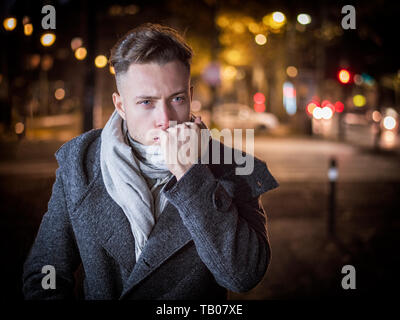 Handsome trendy young man, standing on a sidewalk at night - Stock Image